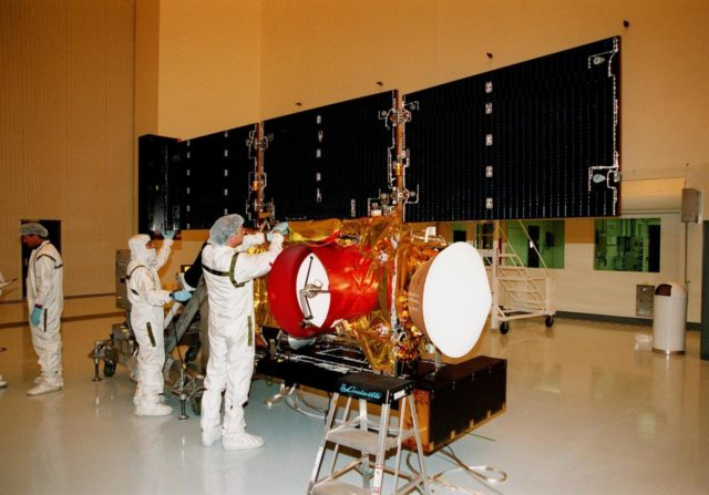"""In the Payload Hazardous Servicing Facility, workers adjust the solar panels of the <a href=""""http://www-pao.ksc.nasa.gov/kscpao/captions/subjects/stardust.htm""""> Stardust</a>spacecraft before performing lighting tests. Stardust is scheduled to be launched aboard a Boeing Delta II rocket from Launch Pad 17A, Cape Canaveral Air Station, on Feb. 6, 1999, for a rendezvous with the comet Wild 2 in January 2004. Stardust will use a substance called aerogel to capture comet particles flying off the nucleus of the comet, plus collect interstellar dust for later analysis. The collected samples will return to Earth in a sample return capsule to be jettisoned as it swings by Earth in January 2006 KSC-99pc43"""