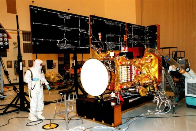 """In the Payload Hazardous Servicing Facility, a worker looks over the solar panels of the <a href=""""http://www-pao.ksc.nasa.gov/kscpao/captions/subjects/stardust.htm""""> Stardust</a> spacecraft before it undergoes lighting tests. Stardust is scheduled to be launched aboard a Boeing Delta II rocket from Launch Pad 17A, Cape Canaveral Air Station, on Feb. 6, 1999, for a rendezvous with the comet Wild 2 in January 2004. Stardust will use a substance called aerogel to capture comet particles flying off the nucleus of the comet, plus collect interstellar dust for later analysis. The collected samples will return to Earth in a sample return capsule (its white cap is seen on the left) to be jettisoned as it swings by Earth in January 2006 KSC-99pc44"""
