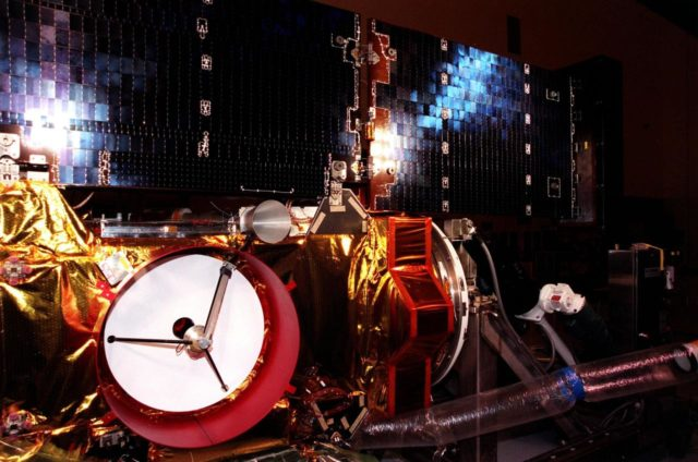 """Bright white light (left) and blue light (upper right) appear on the solar panels of the <a href=""""http://www-pao.ksc.nasa.gov/kscpao/captions/subjects/stardust.htm""""> Stardust</a> spacecraft during lighting tests in the Payload Hazardous Servicing Facility. Stardust is scheduled to be launched aboard a Boeing Delta II rocket from Launch Pad 17A, Cape Canaveral Air Station, on Feb. 6, 1999, for a rendezvous with the comet Wild 2 in January 2004. Stardust will use a substance called aerogel to capture comet particles flying off the nucleus of the comet, plus collect interstellar dust for later analysis. The collected samples will return to Earth in a sample return capsule to be jettisoned as it swings by Earth in January 2006 KSC-99pc45"""