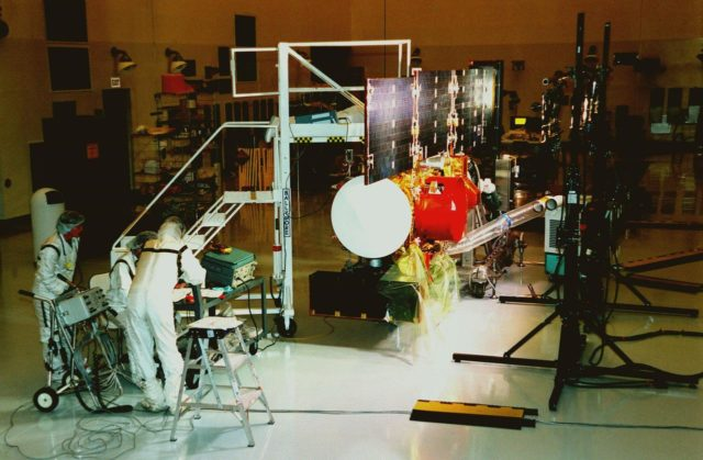 """In the Payload Hazardous Servicing Facility, workers at left check instruments during a lighting test on the solar panels of the <a href=""""http://www-pao.ksc.nasa.gov/kscpao/captions/subjects/stardust.htm""""> Stardust</a>spacecraft. Stardust is scheduled to be launched aboard a Boeing Delta II rocket from Launch Pad 17A, Cape Canaveral Air Station, on Feb. 6, 1999, for a rendezvous with the comet Wild 2 in January 2004. Stardust will use a substance called aerogel to capture comet particles flying off the nucleus of the comet, plus collect interstellar dust for later analysis. The collected samples will return to Earth in a sample return capsule (its white cap is seen on the near end of the spacecraft) to be jettisoned as it swings by Earth in January 2006 KSC-99pc46"""