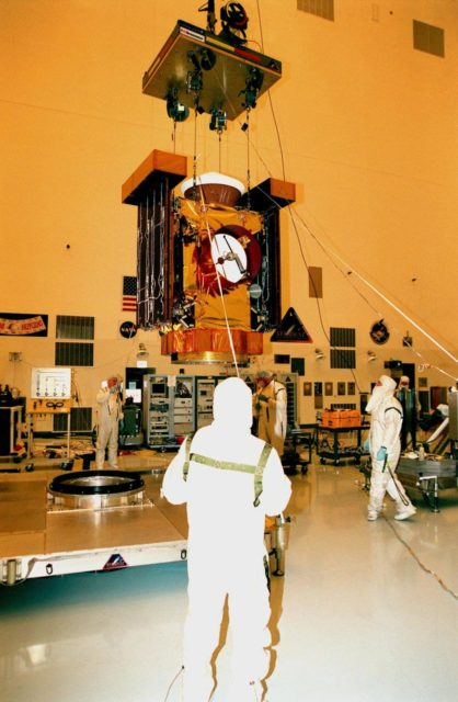 """In the Payload Hazardous Servicing Facility, workers raise the <a href=""""http://www-pao.ksc.nasa.gov/kscpao/captions/subjects/stardust.htm""""> Stardust</a> spacecraft from its workstand to move it to another area for lighting tests on the solar panels. Stardust is scheduled to be launched aboard a Boeing Delta II rocket from Launch Pad 17A, Cape Canaveral Air Station, on Feb. 6, 1999, for a rendezvous with the comet Wild 2 in January 2004. Stardust will use a substance called aerogel to capture comet particles flying off the nucleus of the comet, plus collect interstellar dust for later analysis. The collected samples will return to Earth in a sample return capsule to be jettisoned as it swings by Earth in January 2006 KSC-99pc47"""