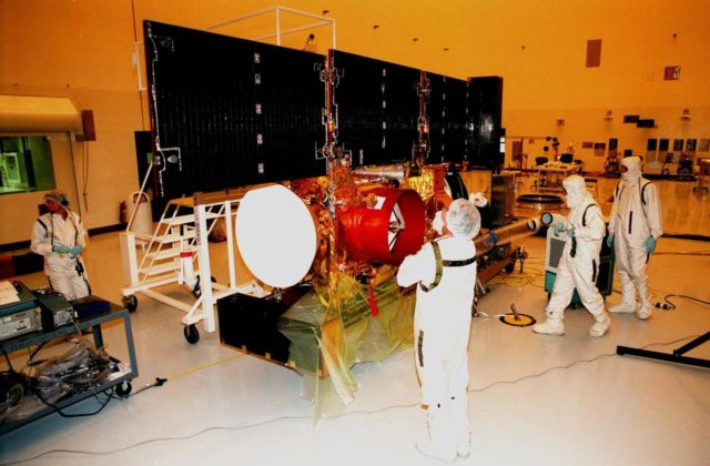 """In the Payload Hazardous Servicing Facility, workers look over the solar panels on the <a href=""""http://www-pao.ksc.nasa.gov/kscpao/captions/subjects/stardust.htm""""> Stardust</a> spacecraft that are deployed for lighting tests. Stardust is scheduled to be launched aboard a Boeing Delta II rocket from Launch Pad 17A, Cape Canaveral Air Station, on Feb. 6, 1999, for a rendezvous with the comet Wild 2 in January 2004. Stardust will use a substance called aerogel to capture comet particles flying off the nucleus of the comet, plus collect interstellar dust for later analysis. The collected samples will return to Earth in a sample return capsule to be jettisoned as it swings by Earth in January 2006 KSC-99pc49"""
