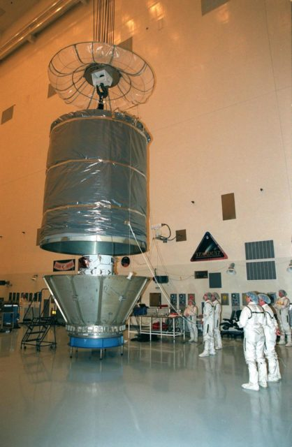 The cover is removed from the Stardust spacecraft in the Payload Hazardous Servicing Facility prior to a media presentation. Stardust is targeted for launch on Feb. 6 aboard a Boeing Delta II rocket from Launch Pad 17-A, Cape Canaveral Air Station. The spacecraft is destined for a close encounter with the comet Wild 2 in January 2004. Using a silicon-based substance called aerogel, Stardust will capture comet particles flying off the nucleus of the comet. The spacecraft also will bring back samples of interstellar dust. These materials consist of ancient pre-solar interstellar grains and other remnants left over from the formation of the solar system. Scientists expect their analysis to provide important insights into the evolution of the sun and planets and possibly into the origin of life itself. The collected samples will return to Earth in a sample return capsule (the white-topped, blunt-nosed cone seen on the top of the spacecraft) to be jettisoned as Stardust swings by Earth in January 2006 KSC-99pc0093