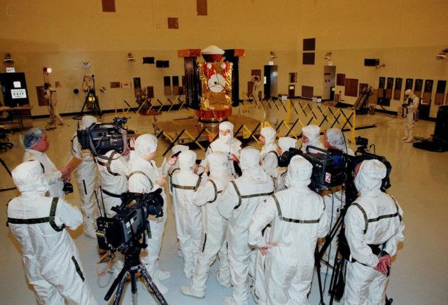 In the Payload Hazardous Servicing Facility, media representatives, dressed in protective suits, are updated by Project Manager Richard Grammier (center, top), with the Jet Propulsion Laboratory, about the Stardust spacecraft (in the background). Stardust is targeted for launch on Feb. 6 aboard a Boeing Delta II rocket from Launch Pad 17-A, Cape Canaveral Air Station. The spacecraft is destined for a close encounter with the comet Wild 2 in January 2004. Using a silicon-based substance called aerogel, Stardust will capture comet particles flying off the nucleus of the comet. The spacecraft also will bring back samples of interstellar dust. These materials consist of ancient pre-solar interstellar grains and other remnants left over from the formation of the solar system. Scientists expect their analysis to provide important insights into the evolution of the sun and planets and possibly into the origin of life itself. The collected samples will return to Earth in a sample return capsule (the white-topped, blunt-nosed cone seen on the top of the spacecraft) to be jettisoned as Stardust swings by Earth in January 2006 KSC-99pc0096