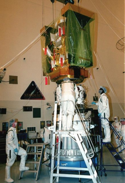 In the Payload Hazardous Servicing Facility, workers help guide the spacecraft Stardust being lowered in order to mate it with the third stage of a Boeing Delta II rocket. Targeted for launch Feb. 6 from Launch Pad 17-A, Cape Canaveral Air Station, aboard the Delta II rocket, the spacecraft is destined for a close encounter with the comet Wild 2 in January 2004. Using a silicon-based substance called aerogel, Stardust will capture comet particles flying off the nucleus of the comet. The spacecraft also will bring back samples of interstellar dust. These materials consist of ancient pre-solar interstellar grains and other remnants left over from the formation of the solar system. Scientists expect their analysis to provide important insights into the evolution of the sun and planets and possibly into the origin of life itself. The collected samples will return to Earth in a sample return capsule to be jettisoned as Stardust swings by Earth in January 2006 KSC-99pc0101