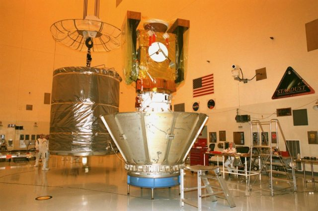 In the Payload Hazardous Servicing Facility, a canister (left) is moved toward the Stardust spacecraft (right). The protective canister will enclose Stardust before the spacecraft is moved to Launch Pad 17-A, Cape Canaveral Air Station, for launch preparations. Stardust is targeted for liftoff on Feb. 6 aboard a Boeing Delta II rocket for a close encounter with the comet Wild 2 in January 2004. Using a silicon-based substance called aerogel, Stardust will capture comet particles flying off the nucleus of the comet. The spacecraft also will bring back samples of interstellar dust. These materials consist of ancient pre-solar interstellar grains and other remnants left over from the formation of the solar system. Scientists expect their analysis to provide important insights into the evolution of the sun and planets and possibly into the origin of life itself. The collected samples will return to Earth in a sample return capsule to be jettisoned as Stardust swings by Earth in January 2006 KSC-99pc0121