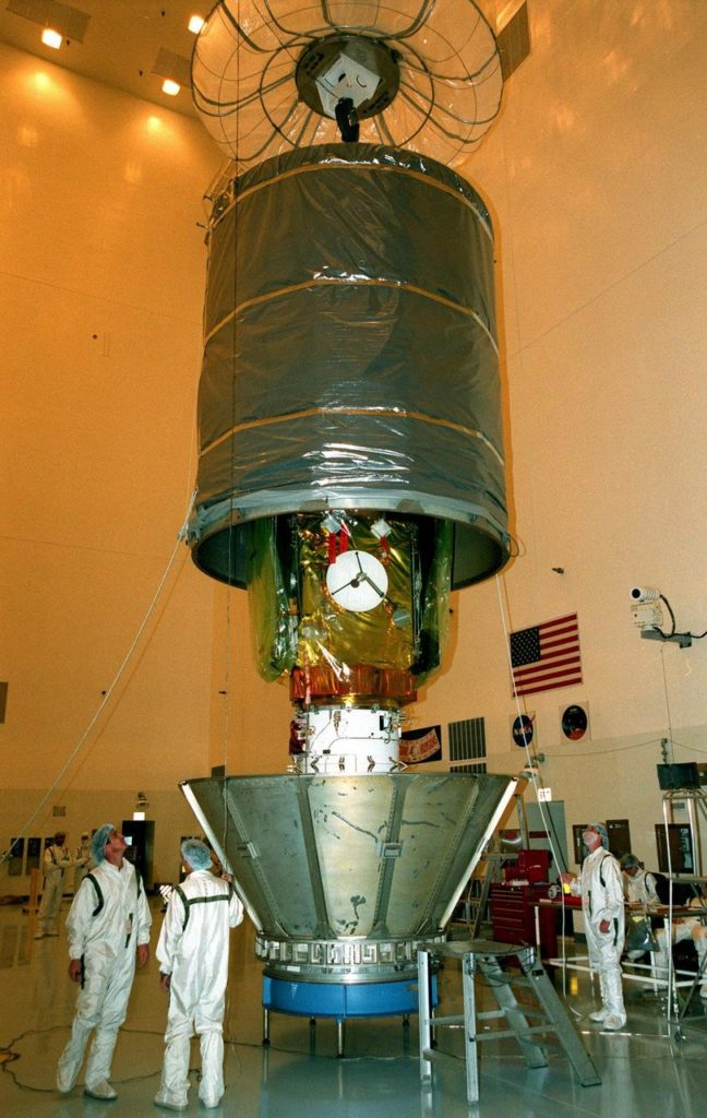 In the Payload Hazardous Servicing Facility, workers guide a protective canister as it is lowered over the Stardust spacecraft. Once it is enclosed, Stardust will be moved to Launch Pad 17-A, Cape Canaveral Air Station, for launch preparations. Stardust is targeted for liftoff on Feb. 6 aboard a Boeing Delta II rocket for a close encounter with the comet Wild 2 in January 2004. Using a silicon-based substance called aerogel, Stardust will capture comet particles flying off the nucleus of the comet. The spacecraft also will bring back samples of interstellar dust. These materials consist of ancient pre-solar interstellar grains and other remnants left over from the formation of the solar system. Scientists expect their analysis to provide important insights into the evolution of the sun and planets and possibly into the origin of life itself. The collected samples will return to Earth in a sample return capsule to be jettisoned as Stardust swings by Earth in January 2006 KSC-99pc0122