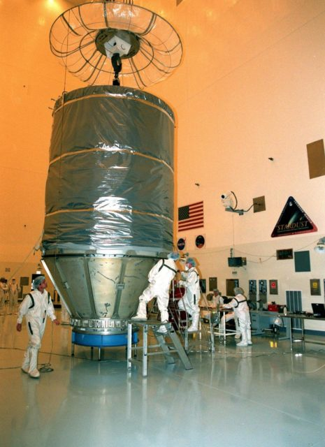 In the Payload Hazardous Servicing Facility, workers check the final adjustments on the protective canister enclosing the Stardust spacecraft. Stardust will be moved to Launch Pad 17-A, Cape Canaveral Air Station, for launch preparations. The spacecraft is targeted for liftoff on Feb. 6 aboard a Boeing Delta II rocket for a close encounter with the comet Wild 2 in January 2004. Using a silicon-based substance called aerogel, Stardust will capture comet particles flying off the nucleus of the comet. The spacecraft also will bring back samples of interstellar dust. These materials consist of ancient pre-solar interstellar grains and other remnants left over from the formation of the solar system. Scientists expect their analysis to provide important insights into the evolution of the sun and planets and possibly into the origin of life itself. The collected samples will return to Earth in a sample return capsule to be jettisoned as Stardust swings by Earth in January 2006 KSC-99pc0123
