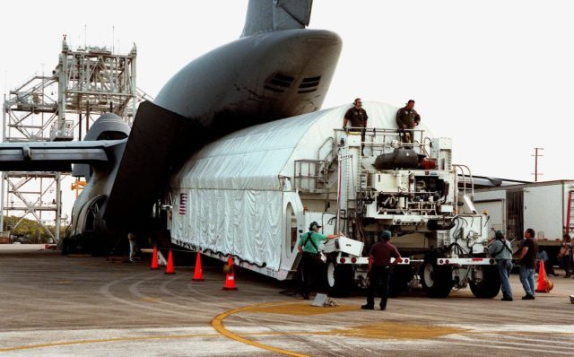 KENNEDY SPACE CENTER, FLA. -- The Chandra X-ray Observatory is unloaded from an Air Force C-5 Galaxy transporter two days after landing at the Shuttle Landing Facility on Feb. 4. The observatory sits cradled in the cargo hold of a tractor-trailer rig called the Space Cargo Transportation System, which closely resembles the size and shape of the Shuttle cargo bay. In the background (left) is the mate-demate device, used when an orbiter is returned to KSC on the back of a Shuttle carrier aircraft. Over the next few months, Chandra will undergo final tests and be mated to a Boeing-provided Inertial Upper Stage for launch July 9 aboard Space Shuttle Columbia, on mission STS-93 . Formerly called the Advanced X-ray Astrophysics Facility, Chandra comprises three major elements: the spacecraft, the science instrument module (SIM), and the world's most powerful X-ray telescope. Chandra will allow scientists from around the world to see previously invisible black holes and high-temperature gas clouds, giving the observatory the potential to rewrite the books on the structure and evolution of our universe KSC-99pc0164