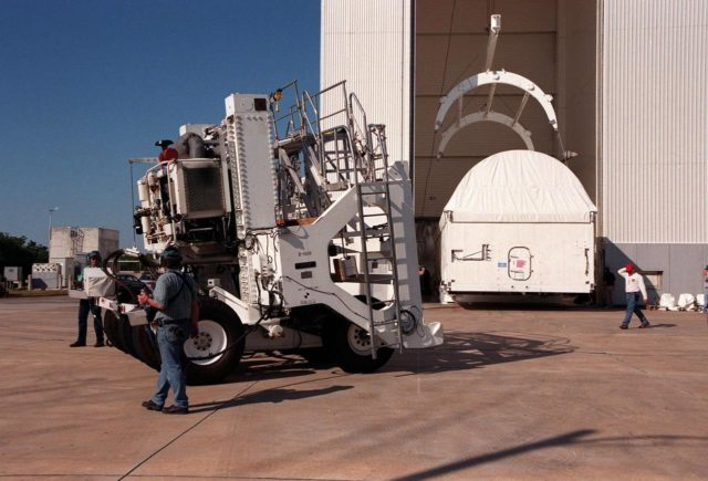 At the Vertical Processing Facility (VPF), workers (left) drive, by remote control, the rear bogie away from the VPF. The bogie is part of the tractor-trailer rig called the Space Cargo Transportation System that helped move the Chandra X-ray Observatory (right) from the Shuttle Landing Facility into the VPF. Chandra arrived at KSC on Thursday, Feb. 4, aboard an Air Force C-5 Galaxy aircraft. In the VPF, the telescope will undergo final installation of associated electronic components; it will also be tested, fueled and mated with the Inertial Upper Stage booster. A set of integrated tests will follow. Chandra is scheduled for launch July 9 aboard Space Shuttle Columbia, on mission STS-93 . Formerly called the Advanced X-ray Astrophysics Facility, Chandra comprises three major elements: the spacecraft, the science instrument module (SIM), and the world's most powerful X-ray telescope. Chandra will allow scientists from around the world to see previously invisible black holes and high-temperature gas clouds, giving the observatory the potential to rewrite the books on the structure and evolution of our universe KSC-99pc0167
