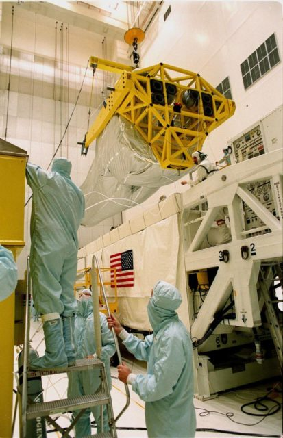 In the Vertical Processing Facility (VPF), workers begin moving the overhead crane carrying the Chandra X-ray Observatory from its protective container to a stand on the floor. While in the VPF, the telescope will undergo final installation of associated electronic components; it will also be tested, fueled and mated with the Inertial Upper Stage booster. A set of integrated tests will follow. Chandra is scheduled for launch July 9 aboard Space Shuttle Columbia, on mission STS-93 . Formerly called the Advanced X-ray Astrophysics Facility, Chandra comprises three major elements: the spacecraft, the science instrument module (SIM), and the world's most powerful X-ray telescope. Chandra will allow scientists from around the world to see previously invisible black holes and high-temperature gas clouds, giving the observatory the potential to rewrite the books on the structure and evolution of our universe KSC-99pc0173