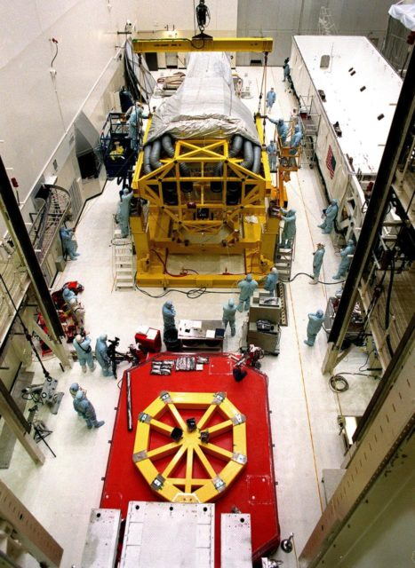 In the Vertical Processing Facility (VPF), workers check the placement of the Chandra X-ray Observatory on the stand on the floor. The stand will be used to raise the observatory to a vertical position. While in the VPF, the telescope will undergo final installation of associated electronic components; it will also be tested, fueled and mated with the Inertial Upper Stage booster. A set of integrated tests will follow. Chandra is scheduled for launch July 9 aboard Space Shuttle Columbia, on mission STS-93 . Formerly called the Advanced X-ray Astrophysics Facility, Chandra comprises three major elements: the spacecraft, the science instrument module (SIM), and the world's most powerful X-ray telescope. Chandra will allow scientists from around the world to see previously invisible black holes and high-temperature gas clouds, giving the observatory the potential to rewrite the books on the structure and evolution of our universe KSC-99pc0174