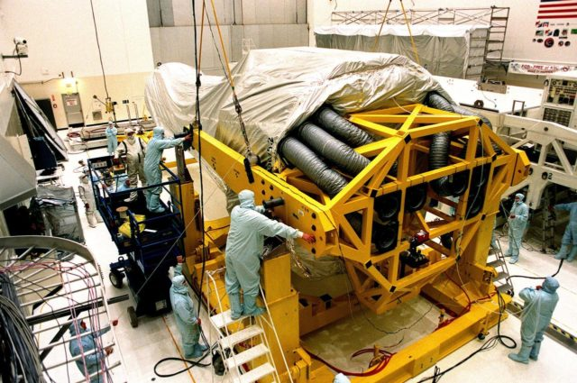 In the Vertical Processing Facility (VPF), workers check fittings and cables on the stand that will raise the Chandra X-ray Observatory to a vertical position. While in the VPF, the telescope will undergo final installation of associated electronic components; it will also be tested, fueled and mated with the Inertial Upper Stage booster. A set of integrated tests will follow. Chandra is scheduled for launch July 9 aboard Space Shuttle Columbia, on mission STS-93 . Formerly called the Advanced X-ray Astrophysics Facility, Chandra comprises three major elements: the spacecraft, the science instrument module (SIM), and the world's most powerful X-ray telescope. Chandra will allow scientists from around the world to see previously invisible black holes and high-temperature gas clouds, giving the observatory the potential to rewrite the books on the structure and evolution of our universe KSC-99pc0175