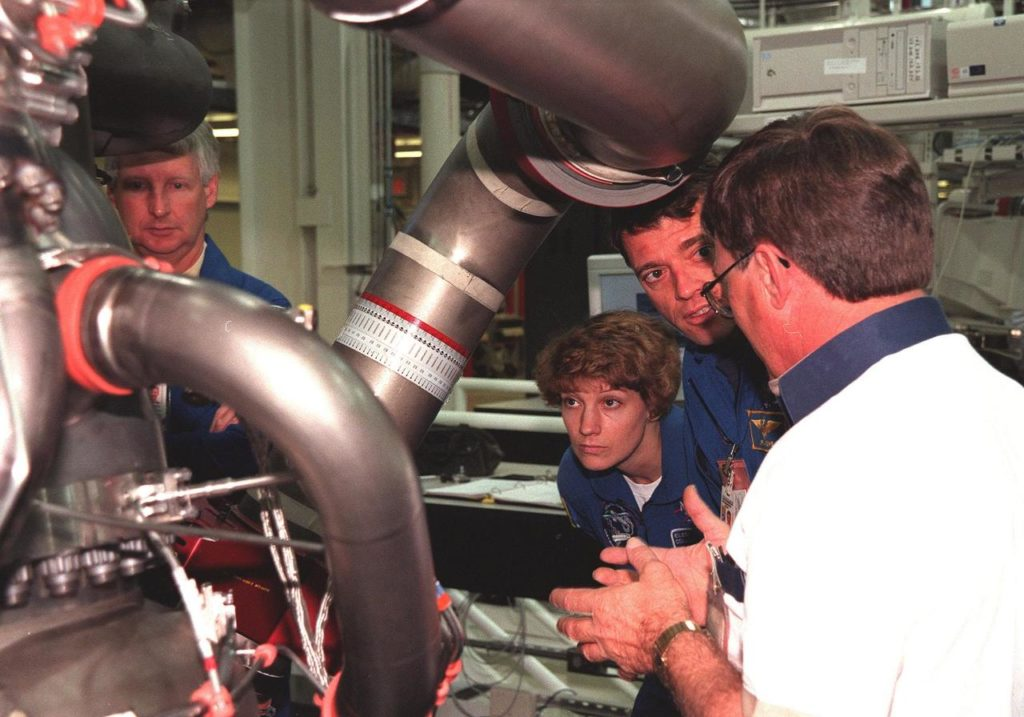 In the Space Shuttle Main Engine Facility, STS-93 crew members listen to Site Director Dan Hausman, with Rocketdyne, while looking over the main engine of the Space Shuttle Columbia. From left, they are Mission Specialist Steven A. Hawley, Commander Eileen Collins and Pilot Jeffrey S. Ashby. Other crew members (not shown) are Mission Specialist Michel Tognini of France, who represents the Centre National d'Etudes Spatiales (CNES), and Mission Specialist Catherine G. Coleman. STS-93, scheduled to launch July 9 aboard Space Shuttle Columbia, has the primary mission of the deployment of the Chandra X-ray Observatory. Formerly called the Advanced X-ray Astrophysics Facility, Chandra comprises three major elements: the spacecraft, the science instrument module (SIM), and the world's most powerful X-ray telescope. Chandra will allow scientists from around the world to see previously invisible black holes and high-temperature gas clouds, giving the observatory the potential to rewrite the books on the structure and evolution of our universe KSC-99pc0178