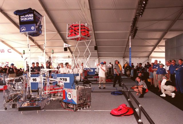 Four robots vie for position on the playing field during the 1999 FIRST Southeastern Regional robotic competition held at KSC. Powered by 12-volt batteries and operated by remote control, the robotic gladiators spent two minutes each trying to grab, claw and hoist large, satin pillows onto their machines. Student teams, shown behind protective walls, play defense by taking away competitors' pillows and generally harassing opposing machines. Two of the robots have lifted their caches of pillows above the field, a movement which earns them points. Along with the volunteer referees, at the edge of the playing field, judges at right watch the action. FIRST is a nonprofit organization, For Inspiration and Recognition of Science and Technology. The competition comprised 27 teams, pairing high school students with engineer mentors and corporations. The FIRST robotics competition is designed to provide students with a hands-on, inside look at engineering and other professional careers KSC-99pd0278