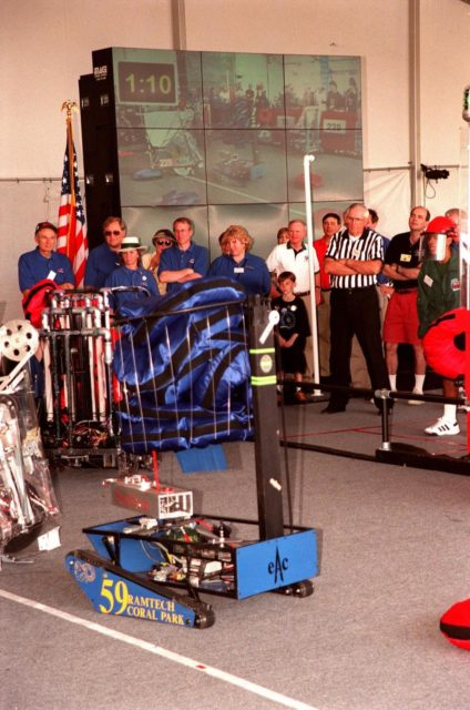 During the 1999 FIRST Southeastern Regional robotic competition held at KSC, a robot carrying its cache of pillow-like disks maneuvers to move around another at left. Powered by 12-volt batteries and operated by remote control, the robotic gladiators spend two minutes each trying to grab, claw and hoist the pillows onto their machines. Teams play defense by taking away competitors' pillows and generally harassing opposing machines. Behind the field are a group of judges, including KSC former KSC Director of Shuttle Processing Robert Sieck (left, in cap), and Center Director Roy Bridges (in white shirt). A giant screen TV in the background displays the action on the playing field. FIRST is a nonprofit organization, For Inspiration and Recognition of Science and Technology. The competition comprised 27 teams, pairing high school students with engineer mentors and corporations. The FIRST robotics competition is designed to provide students with a hands-on, inside look at engineering and other professional careers KSC-99pp0277