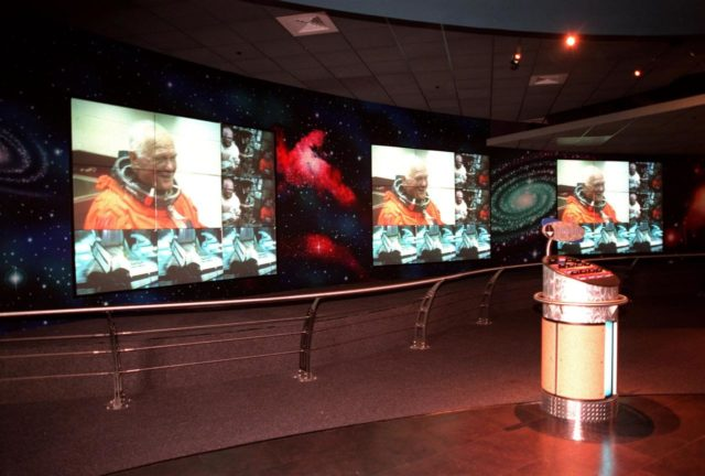 KENNEDY SPACE CENTER, FLA. -- Part of the $13 million expansion to KSC's Visitor Complex, the new information center welcomes visitors to the Gateway to the Universe. The five large video walls provide an orientation video, shown here with photos of John Glenn in his historic Shuttle mission in October 1998, with an introduction to the range of activities and exhibits, plus honor the center's namesake, President John F. Kennedy. Other new additions include a walk-through Robot Scouts exhibit, a wildlife exhibit, and the film Quest for Life in a new 300-seat theater, plus an International Space Station-themed ticket plaza, featuring a structure of overhanging solar panels and astronauts performing assembly tasks. The KSC Visitor Complex was inaugurated three decades ago and is now one of the top five tourist attractions in Florida. It is located on S.R. 407, east of I-95, within the Merritt Island National Wildlife Refuge KSC-99pp0403