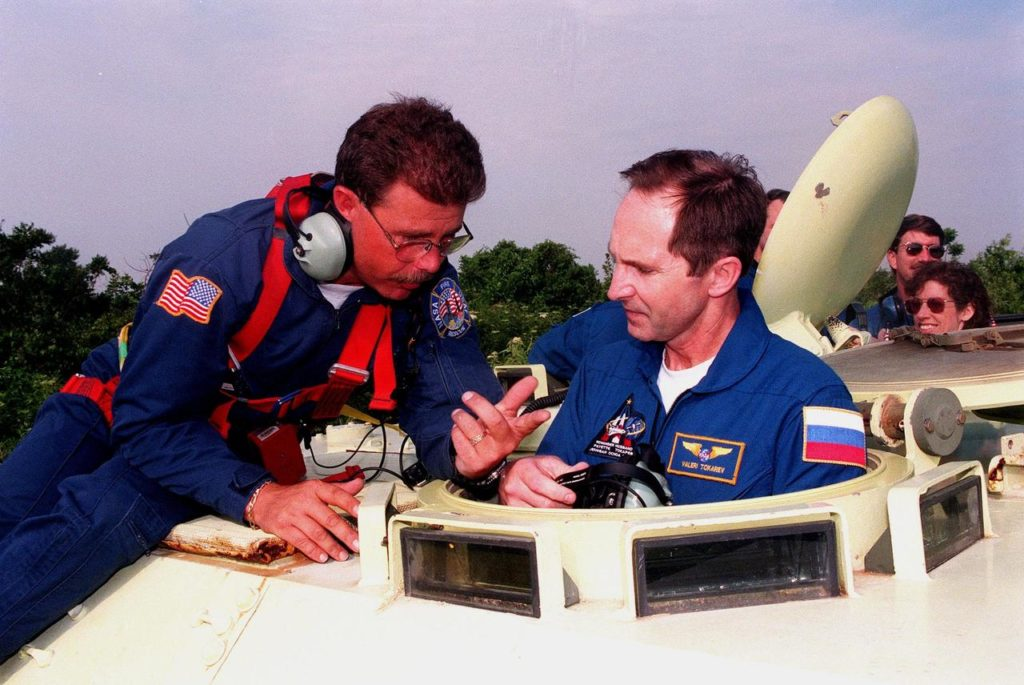 Capt. Steve Kelly (left), with Space Gateway Support, explains to STS-96 Mission Specialist Valery Ivanovich Tokarev the use of the small armored personnel carrier that is part of emergency egress training during Terminal Countdown Demonstration Test (TCDT) activities. Behind him are Commander Kent V. Rominger and Mission Specialist Ellen Ochoa (Ph.D.). The tracked vehicle could be used by the crew in the event of an emergency at the pad during which the crew must make a quick exit from the area. The TCDT also provides simulated countdown exercises and opportunities to inspect the mission payloads in the orbiter's payload bay. Other crew members taking part in the TCDT are Pilot Rick Douglas Husband and Mission Specialists Tamara E. Jernigan (Ph.D.), Daniel Barry (M.D., Ph.D.), and Julie Payette, with the Canadian Space Agency. Tokarev is with the Russian Space Agency. Mission STS-96, which is scheduled for liftoff on May 20 at 9:32 a.m., is a logistics and resupply mission for the International Space Station, carrying such payloads as a Russian crane, the Strela; a U.S.-built crane; the Spacehab Oceaneering Space System Box (SHOSS), a logistics items carrier; and STARSHINE, a student-led experiment KSC-99pp0456