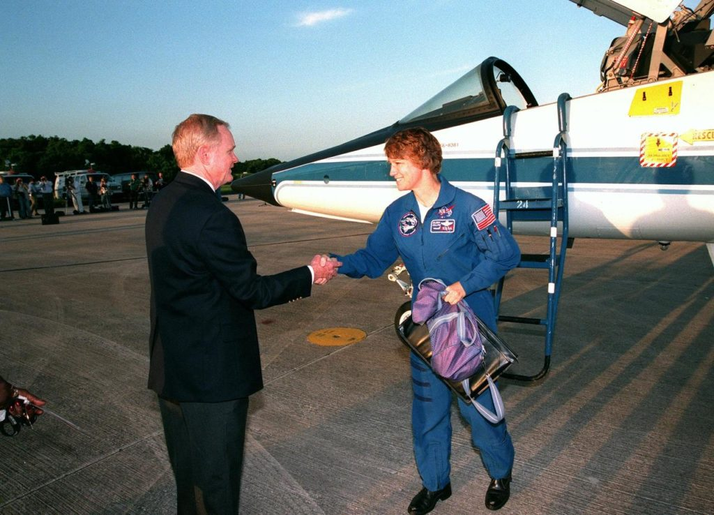 """Center Director Roy D. Bridges Jr. greets STS-93 Commander Eileen M. Collins after her arrival at KSC's Shuttle Landing Facility aboard a T-38 jet aircraft (behind her). She and other crew members Pilot Jeffrey S. Ashby and Mission Specialists Steven A. Hawley (Ph.D.), Catherine G. """"Cady"""" Coleman (Ph.D.) and Michel Tognini of France, with the Centre National d'Etudes Spatiales (CNES), are arriving for pre-launch activities. Collins is the first woman to serve as mission commander. This is her third Shuttle flight. The primary mission of STS-93 is the release of the Chandra X-ray Observatory, which will allow scientists from around the world to study some of the most distant, powerful and dynamic objects in the universe. The new telescope is 20 to 50 times more sensitive than any previous X-ray telescope and is expected to unlock the secrets of supernovae, quasars and black holes KSC-99pp0826"""