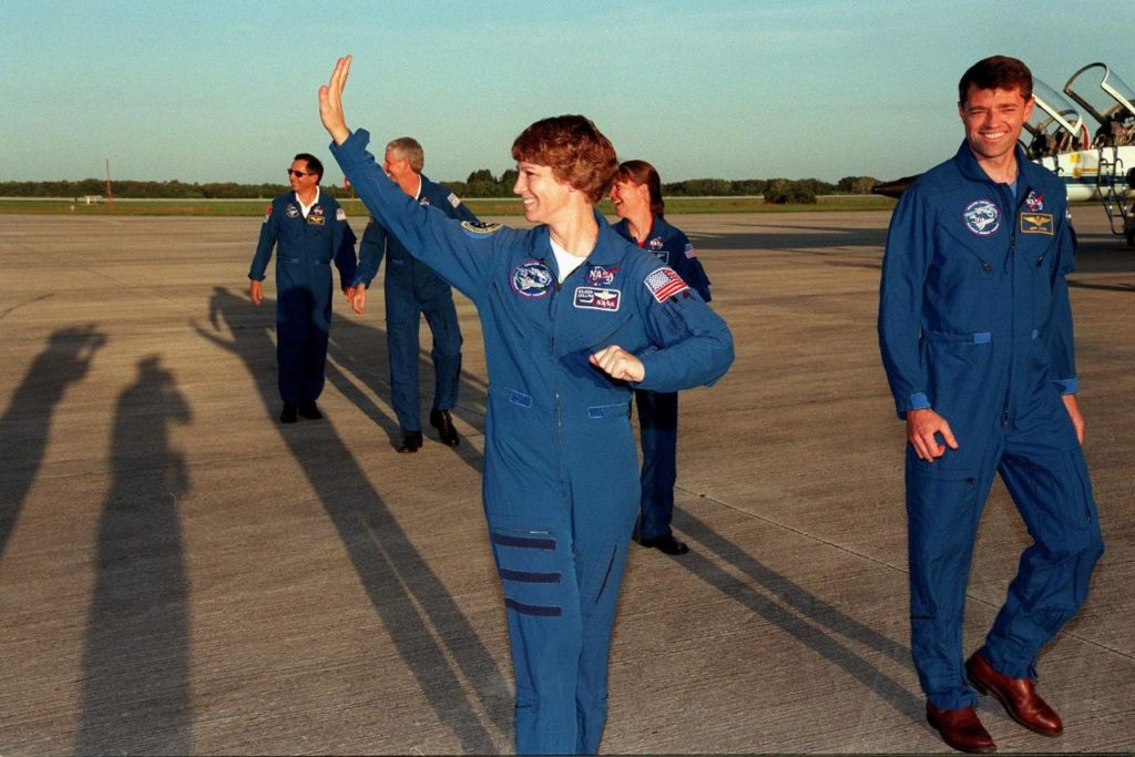"""The STS-93 crew leave the Shuttle Landing Facility after answering questions for the media and posing for photographers, whose shadows stretch across the SLF. From left are Mission Specialists Michel Tognini of France, who is with the Centre National d'Etudes Spatiales (CNES) and Steven A. Hawley (Ph.D.), Commander Eileen M. Collins (waving), Mission Specialist Catherine G. """"Cady"""" Coleman (Ph.D.), and Pilot Jeffrey S. Ashby. The crew arrived at KSC for pre-launch activities. Collins is the first woman to serve as mission commander. The primary mission of STS-93 is the release of the Chandra X-ray Observatory, which will allow scientists from around the world to study some of the most distant, powerful and dynamic objects in the universe. The new telescope is 20 to 50 times more sensitive than any previous X-ray telescope and is expected to unlock the secrets of supernovae, quasars and black holes KSC-99pp0830"""