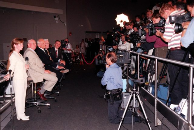 """KENNEDY SPACE CENTER, FLA. -- In the Apollo/Saturn V Center, Lisa Malone (left), chief of KSC's Media Services branch, waits for photographers to take photos of former Apollo astronauts (left to right) Neil A. Armstrong and Edwin """"Buzz"""" Aldrin who flew on Apollo 11, the launch to the moon; Gene Cernan, who flew on Apollo 10 and 17; and Walt Cunningham, who flew on Apollo 7. The four met with the media prior to an anniversary banquet highlighting the contributions of aerospace employees who made the Apollo program possible. The banquet celebrated the 30th anniversary of the launch and moon landing, July 16 and July 20, 1969. Neil Armstrong was the first man to set foot on the moon KSC-99pp0841"""