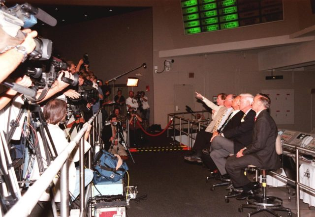 """KENNEDY SPACE CENTER, FLA. -- In the Apollo/Saturn V Center, Lisa Malone, chief of KSC's Media Services branch, identifies a reporter in the stands to pose a question to one of the former Apollo astronauts seated next to her. From left to right, they are Neil A. Armstrong and Edwin """"Buzz"""" Aldrin who flew on Apollo 11, the launch to the moon; Gene Cernan, who flew on Apollo 10 and 17; and Walt Cunningham, who flew on Apollo 7. Behind them on the lower floor are the original computer consoles used in the firing room during the Apollo program. They are now part of the reenactment of the Apollo launches in the exhibit at the center. This is the 30th anniversary of the launch and moon landing, July 16 and July 20, 1969. Neil Armstrong was the first man to set foot on the moon KSC-99pp0850"""