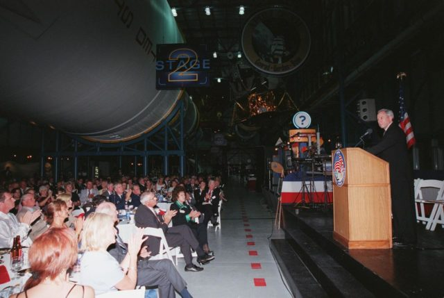 "KENNEDY SPACE CENTER, FLA. -- NASA Administrator Daniel S. Goldin (right) addresses the audience at the Apollo 11 anniversary banquet honoring the Apollo team, the people who made the entire lunar landing program possible. The banquet was held in the Apollo/Saturn V Center, part of the KSC Visitor Complex, with seating under an unused Saturn V rocket like those that powered the Apollo launches . This is the 30th anniversary of the Apollo 11 launch and moon landing, July 16 and July 20, 1969. Among the guests at the banquet were former Apollo astronauts are Neil A. Armstrong and Edwin ""Buzz"" Aldrin who flew on Apollo 11, the launch of the first moon landing; Gene Cernan, who flew on Apollo 10 and 17 and was the last man to walk on the moon; and Walt Cunningham, who flew on Apollo 7 KSC-99pp0875"