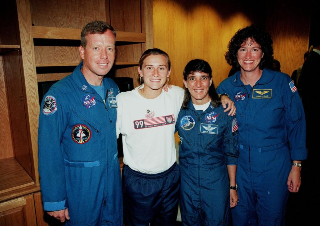 A member of the U.S. Women's World Cup Soccer Team poses with Astronauts (from left) Steven W. Lindsey, Nancy Jane Currie and Laurel B. Clark. The team arrived at the Skid Strip at Cape Canaveral Air Station with First Lady Hillary Rodham Clinton to view the launch of Space Shuttle mission STS-93. Liftoff is scheduled for 12:36 a.m. EDT July 20. Much attention has been generated over the launch due to Commander Eileen M. Collins, the first woman to serve as commander of a Shuttle mission. The primary payload of the five-day mission is the Chandra X-ray Observatory, which will allow scientists from around the world to study some of the most distant, powerful and dynamic objects in the universe. The new telescope is 20 to 50 times more sensitive than any previous X-ray telescope and is expected to unlock the secrets of supernovae, quasars and black holes KSC-99pp0884