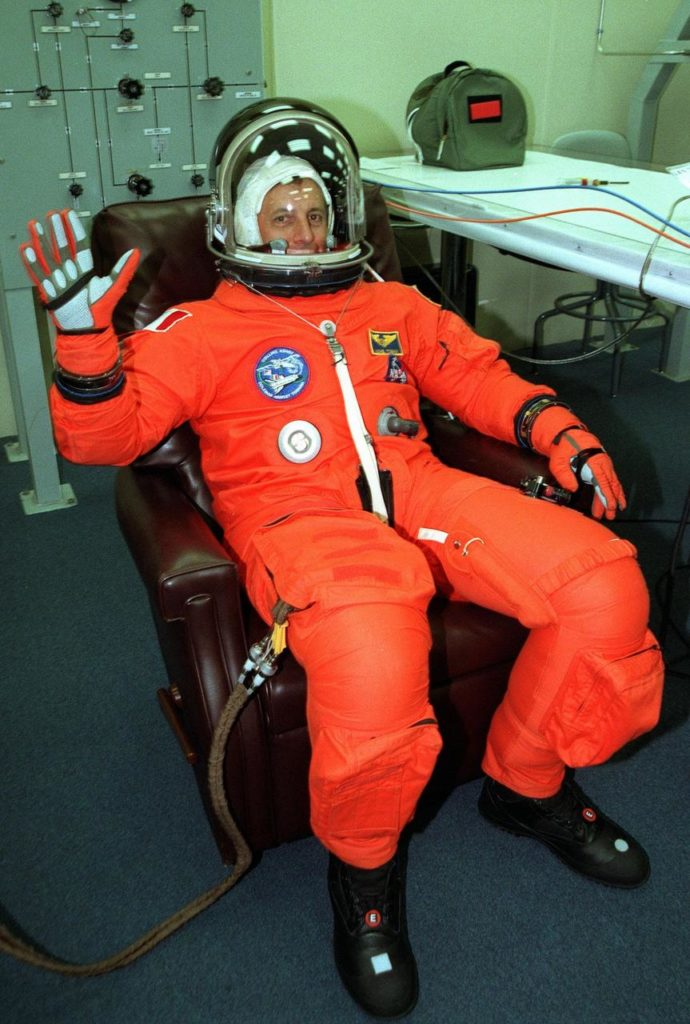 In the Operations and Checkout Building, STS-93 Mission Specialist Michel Tognini of France, who represents the Centre National d'Etudes Spatiales (CNES), waves after donning his launch and entry suit during final launch preparations for the second time. After Space Shuttle Columbia's July 20 launch attempt was scrubbed at the T-7 second mark in the countdown, the launch was rescheduled for Thursday, July 22, at 12:28 a.m. EDT. The target landing date is July 26, 1999, at 11:24 p.m. EDT. STS-93 is a five-day mission primarily to release the Chandra X-ray Observatory, which will allow scientists from around the world to study some of the most distant, powerful and dynamic objects in the universe. The new telescope is 20 to 50 times more sensitive than any previous X-ray telescope and is expected unlock the secrets of supernovae, quasars and black holes. The STS-93 crew numbers five: Commander Eileen M. Collins, Pilot Jeffrey S. Ashby, and Mission Specialists Stephen A. Hawley (Ph.D.), Catherine G. Coleman (Ph.D.) and Tognini. Collins is the first woman to serve as commander of a shuttle mission KSC-99pp0917