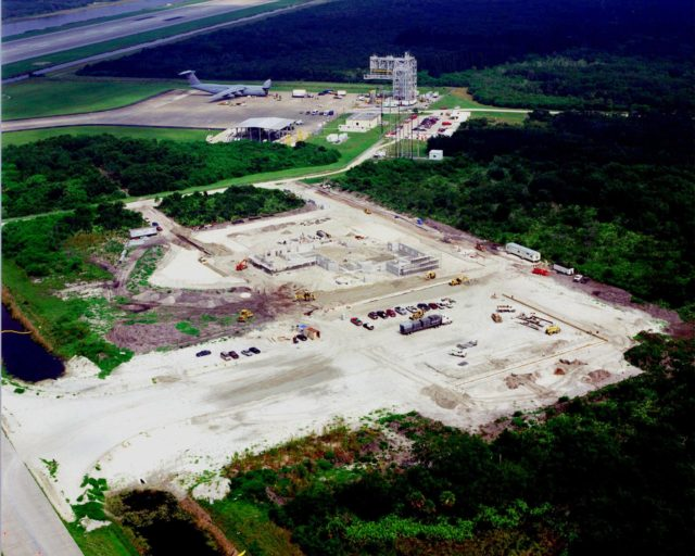 This aerial view shows the construction of a multi-purpose hangar, which is part of the $8 million Reusable Launch Vehicle (RLV) Support Complex at Kennedy Space Center. In the background is the Shuttle Landing Facility, with (left) a C-5 air cargo plane, the offloaded canister in front of it containing the Multi-Purpose Logistics Module Raffaello, and (right) the mate/demate tower that is used when an orbiter is transported to and from KSC atop a modified Boeing 747. The RLV complex will also include facilities for related ground support equipment and administrative/ technical support. It will be available to accommodate the Space Shuttle; the X-34 RLV technology demonstrator; the L-1011 carrier aircraft for Pegasus and X-34; and other RLV and X-vehicle programs. The complex is jointly funded by the Spaceport Florida Authority, NASA's Space Shuttle Program and KSC. The facility will be operational in early 2000. KSC-99pp-1046