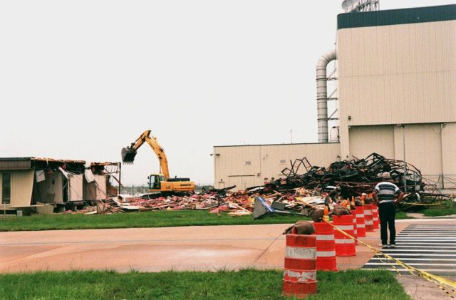 The Butler Building at Kennedy Space Center is nearly demolished, with the help of the crane in the background. The building, which is near the Orbiter Processing Facility (right), is being demolished in order to extend the crawlerway leading to the high bay of the Vehicle Assembly Building (VAB), part of KSC's Safe Haven project. The goal of Safe Haven is to strengthen readiness for Florida's hurricane season by expanding the VAB's storage capacity. Construction includes outfitting the VAB with a third stacking area, in high bay 2, that will allow NASA to preassemble stacks and still have room in the VAB to pull a Shuttle back from the pad into the safety of the VAB if severe weather threatens. The VAB can withstand winds up to 125 mph KSC-99pp1133