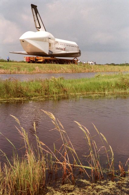 """KENNEDY SPACE CENTER, FLA. -- Aboard a transporter, the orbiter Columbia is moved on the tow-way along the Banana Creek. Columbia is heading to the Shuttle Landing Facility's (SLF) Mate-Demate Device where it will be mated to the Boeing 747 Shuttle Carrier Aircraft for a ferry flight to Palmdale, Calif. On the rear of the orbiter can be seen the tail cone, a fairing that is installed over the aft fuselage of the orbiter to decrease aerodynamic drag and buffet when the Shuttle Carrier Aircraft is transporting the orbiter cross-country. It is 36 feet long, 25 feet wide, and 22 feet high. Columbia, the oldest of four orbiters in NASA's fleet, will undergo extensive inspections and modifications in Boeing's Orbiter Assembly Facility during a nine-month orbiter maintenance down period (OMDP), the second in its history. Orbiters are periodically removed from flight operations for an OMDP. Columbia's first was in 1994. Along with more than 100 modifications on the vehicle, Columbia will be the second orbiter to be outfitted with the multifunctional electronic display system, or """"glass cockpit."""" Columbia is expected to return to KSC in July 2000 KSC-99pp1138"""