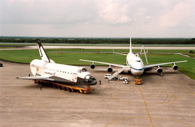 """KENNEDY SPACE CENTER, FLA. -- Aboard a transporter, the orbiter Columbia moves past the Boeing 747 Shuttle Carrier Aircraft (SCA) at the Shuttle Landing Facility. There the orbiter will be mated to the SCA, with the help of a Mate-Demate Device, for a ferry flight to Palmdale, Calif. On the rear of the orbiter is the tail cone, a fairing that is installed over the aft fuselage of the orbiter to decrease aerodynamic drag and buffet when the Shuttle Carrier Aircraft is transporting the orbiter cross-country. It is 36 feet long, 25 feet wide, and 22 feet high. Columbia, the oldest of four orbiters in NASA's fleet, will undergo extensive inspections and modifications in Boeing's Orbiter Assembly Facility during a nine-month orbiter maintenance down period (OMDP), the second in its history. Orbiters are periodically removed from flight operations for an OMDP. Columbia's first was in 1994. Along with more than 100 modifications on the vehicle, Columbia will be the second orbiter to be outfitted with the multifunctional electronic display system, or """"glass cockpit."""" Columbia is expected to return to KSC in July 2000 KSC-99pp1139"""