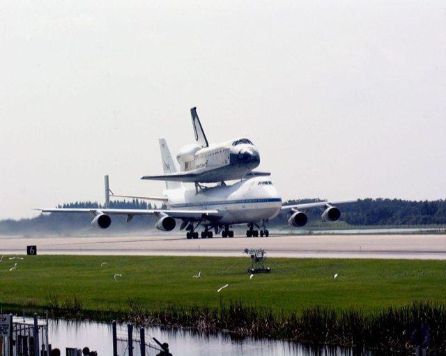 "KENNEDY SPACE CENTER, FLA. -- At the Shuttle Landing Facility, egrets along the runway take flight as the orbiter Columbia leaves Kennedy Space Center on the back of a Boeing 747 Shuttle Carrier Aircraft on a ferry flight to Palmdale, Calif. Columbia, the oldest of four orbiters in NASA's fleet, will undergo extensive inspections and modifications in Boeing's Orbiter Assembly Facility during a nine-month orbiter maintenance down period (OMDP), the second in its history. Orbiters are periodically removed from flight operations for an OMDP. Columbia's first was in 1994. Along with more than 100 modifications on the vehicle, Columbia will be the second orbiter to be outfitted with the multifunctional electronic display system, or ""glass cockpit."" Columbia is expected to return to KSC in July 2000 KSC-99padig007"