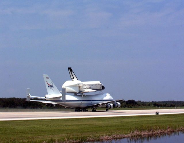 """KENNEDY SPACE CENTER, FLA. -- From the Shuttle Landing Facility at Kennedy Space Center, the orbiter Columbia moves down the runway on the back of a Boeing 747 Shuttle Carrier Aircraft on a ferry flight to Palmdale, Calif. On the rear of the orbiter can be seen the tail cone, a fairing that is installed over the aft fuselage of the orbiter to decrease aerodynamic drag and buffet when the Shuttle Carrier Aircraft is transporting the orbiter cross-country. It is 36 feet long, 25 feet wide, and 22 feet high. Columbia, the oldest of four orbiters in NASA's fleet, will undergo extensive inspections and modifications in Boeing's Orbiter Assembly Facility during a nine-month orbiter maintenance down period (OMDP), the second in its history. Orbiters are periodically removed from flight operations for an OMDP. Columbia's first was in 1994. Along with more than 100 modifications on the vehicle, Columbia will be the second orbiter to be outfitted with the multifunctional electronic display system, or """"glass cockpit."""" Columbia is expected to return to KSC in July 2000 KSC-99padig008"""