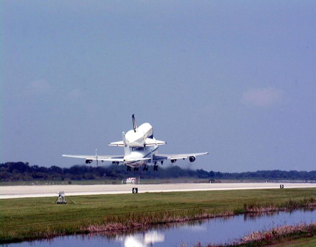 """KENNEDY SPACE CENTER, FLA. -- At the Shuttle Landing Facility at Kennedy Space Center, the orbiter Columbia takes off into a clear sky on the back of a Boeing 747 Shuttle Carrier Aircraft on a ferry flight to Palmdale, Calif. On the rear of the orbiter can be seen the tail cone, a fairing that is installed over the aft fuselage of the orbiter to decrease aerodynamic drag and buffet when the Shuttle Carrier Aircraft is transporting the orbiter cross-country. It is 36 feet long, 25 feet wide, and 22 feet high. Columbia, the oldest of four orbiters in NASA's fleet, will undergo extensive inspections and modifications in Boeing's Orbiter Assembly Facility during a nine-month orbiter maintenance down period (OMDP), the second in its history. Orbiters are periodically removed from flight operations for an OMDP. Columbia's first was in 1994. Along with more than 100 modifications on the vehicle, Columbia will be the second orbiter to be outfitted with the multifunctional electronic display system, or """"glass cockpit."""" Columbia is expected to return to KSC in July 2000 KSC-99padig010"""