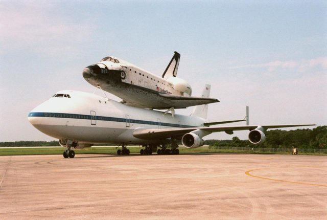 """KENNEDY SPACE CENTER, FLA. -- The Boeing 747 Shuttle Carrier Aircraft, with the orbiter Columbia strapped to its back, waits at the Shuttle Landing Facility for clear weather to take off for its final destination, Palmdale, Calif. The oldest of four orbiters in NASA's fleet, Columbia is being ferried to Palmdale to undergo extensive inspections and modifications in Boeing's Orbiter Assembly Facility. The nine-month orbiter maintenance down period (OMDP) is the second in Columbia's history. Orbiters are periodically removed from flight operations for an OMDP. Columbia's first was in 1994. Along with more than 100 modifications on the vehicle, Columbia will be the second orbiter to be outfitted with the multifunctional electronic display system, or """"glass cockpit."""" Columbia is expected to return to KSC in July 2000 KSC-99pp1142"""