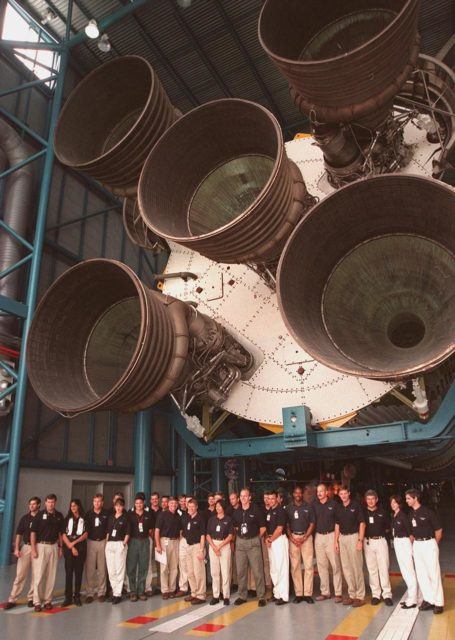 KENNEDY SPACE CENTER, FLA. -- At the Apollo/Saturn V Center, some of the 1998 astronaut candidate class (group 17) line up for a photo while standing under the engines of the Saturn V rocket on display. The U.S. candidates include Clayton C. Anderson, Lee J. Archambault, Tracy E. Caldwell (Ph.D.), Gregory E. Chamitoff (Ph.D.), Timothy J. Creamer, Christopher J. Ferguson, Michael J. Foreman, Michael E. Fossum, Kenneth T. Ham, Patricia C. Hilliard (M.D.), Gregory C. Johnson, Gregory H. Johnson, Stanley G. Love (Ph.D.), Leland D. Melvin, Barbara R. Morgan, William A. Oefelein, John D. Olivas (Ph.D.), Nicholas J.M. Patrick (Ph.D.), Alan G. Poindexter, Garrett E. Reisman (Ph.D.), Steven R. Swanson, Douglas H. Wheelock, Sunita L. Williams, Neil W. Woodward III, George D. Zamka; and international candidates Leopold Eyharts, Paolo Nespoli, Hans Schlegel, Roberto Vittori, Bjarni V. Tryggvason, and Marcos Pontes. The class is at KSC for training activities, including fire training and a flight awareness program, plus touring the OPF, SSME Processing Facility, VAB, SSPF, launch pads, SLF, Apollo/Saturn V Center and the crew headquarters KSC-99pp1144