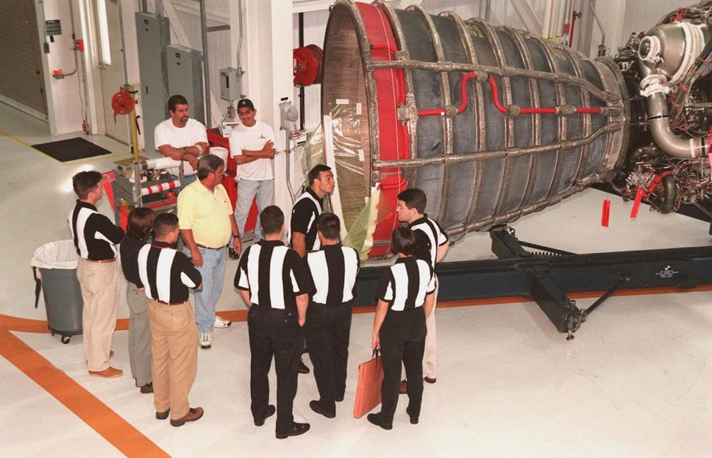 Members of the 1998 astronaut candidate class (group 17) look at the aft of a Space Shuttle Main Engine (SSME) (right). The class is at KSC for training activities, including fire training and a flight awareness program, plus touring the OPF, VAB, SSPF, launch pads, SLF, Apollo/Saturn V Center, the crew headquarters, as well as the SSME Processing Facility. The U.S. candidates in the '98 class are Clayton C. Anderson, Lee J. Archambault, Tracy E. Caldwell (Ph.D.), Gregory E. Chamitoff (Ph.D.), Timothy J. Creamer, Christopher J. Ferguson, Michael J. Foreman, Michael E. Fossum, Kenneth T. Ham, Patricia C. Hilliard (M.D.), Gregory C. Johnson, Gregory H. Johnson, Stanley G. Love (Ph.D.), Leland D. Melvin, Barbara R. Morgan, William A. Oefelein, John D. Olivas (Ph.D.), Nicholas J.M. Patrick (Ph.D.), Alan G. Poindexter, Garrett E. Reisman (Ph.D.), Steven R. Swanson, Douglas H. Wheelock, Sunita L. Williams, Neil W. Woodward III, George D. Zamka; and the international candidates are Leopold Eyharts, Paolo Nespoli, Hans Schlegel, Roberto Vittori, Bjarni V. Tryggvason, and Marcos Pontes KSC-99pp1154