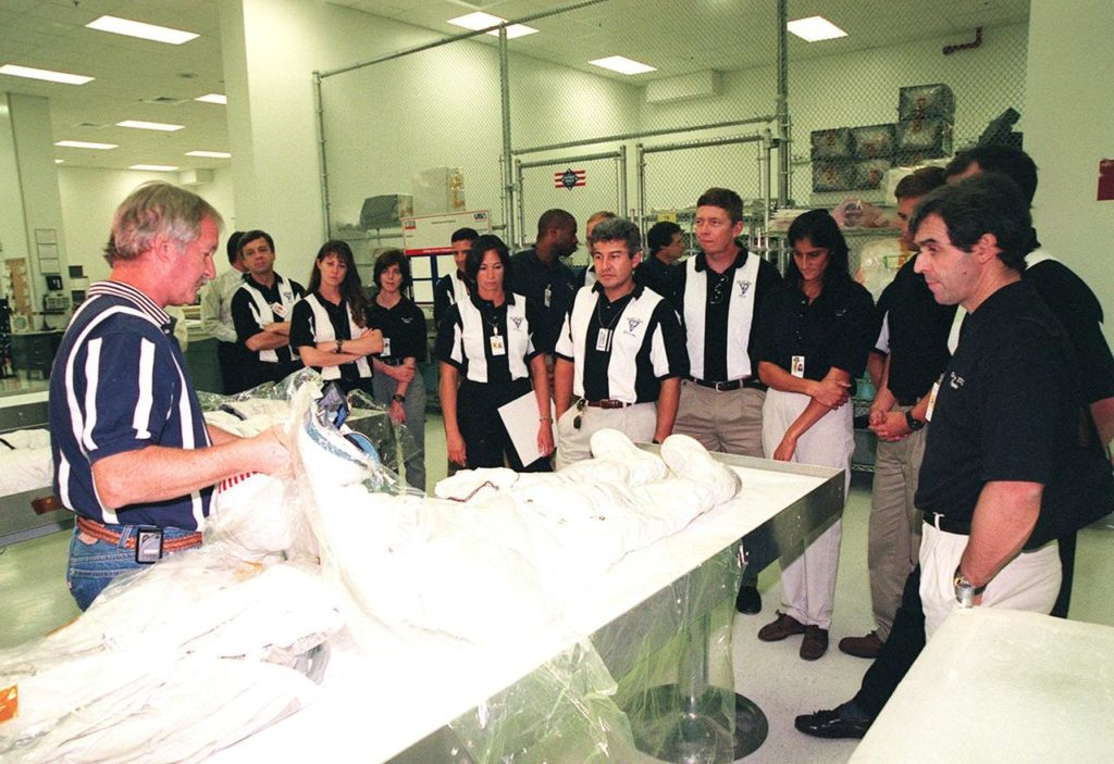 KENNEDY SPACE CENTER, FLA. -- In the Space Station Processing Facility, Ron Woods (left) shows members of the 1998 astronaut candidate class (group 17) an Apollo-style space suit and how it differs from the current suits. The class is taking part in training activities, including fire training and a flight awareness program, plus touring the OPF, VAB, SSPF, launch pads, SLF, Apollo/Saturn V Center, the crew headquarters, as well as the SSME Processing Facility. The U.S. candidates in the '98 class are Clayton C. Anderson, Lee J. Archambault, Tracy E. Caldwell (Ph.D.), Gregory E. Chamitoff (Ph.D.), Timothy J. Creamer, Christopher J. Ferguson, Michael J. Foreman, Michael E. Fossum, Kenneth T. Ham, Patricia C. Hilliard (M.D.), Gregory C. Johnson, Gregory H. Johnson, Stanley G. Love (Ph.D.), Leland D. Melvin, Barbara R. Morgan, William A. Oefelein, John D. Olivas (Ph.D.), Nicholas J.M. Patrick (Ph.D.), Alan G. Poindexter, Garrett E. Reisman (Ph.D.), Steven R. Swanson, Douglas H. Wheelock, Sunita L. Williams, Neil W. Woodward III, George D. Zamka; and the international candidates are Leopold Eyharts, Paolo Nespoli, Hans Schlegel, Roberto Vittori, Bjarni V. Tryggvason, and Marcos Pontes KSC-99pp1156
