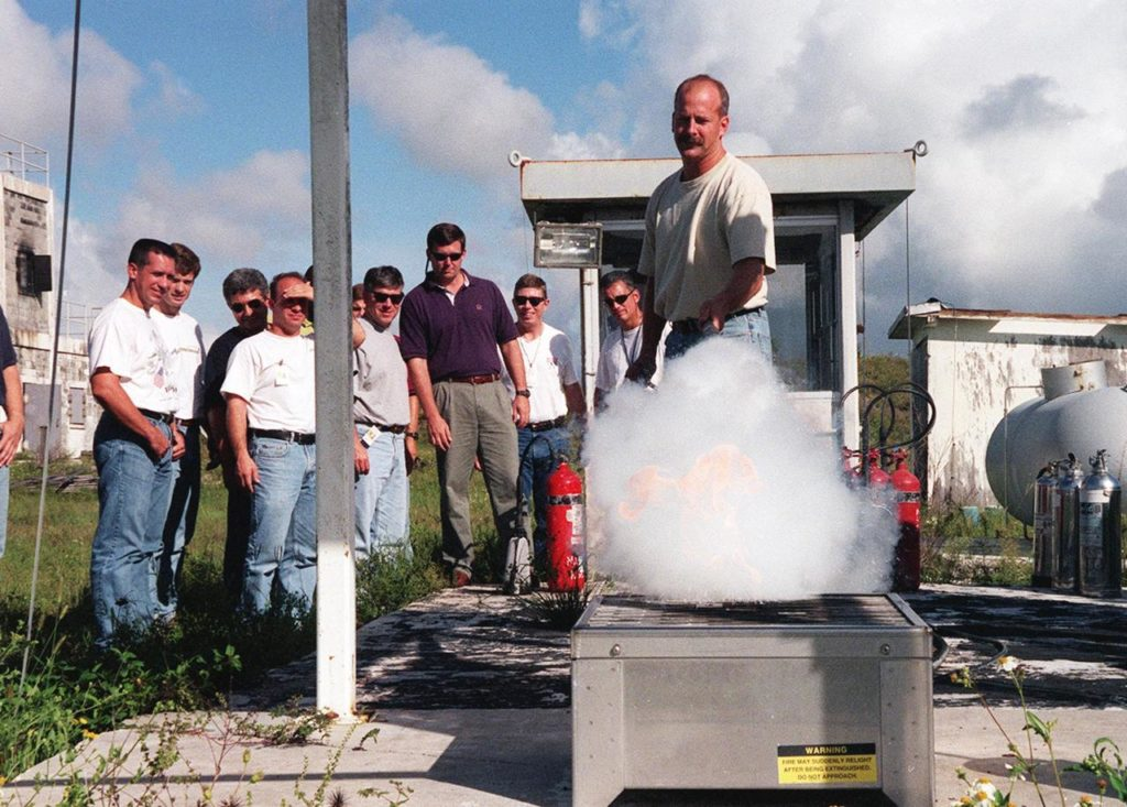 KENNEDY SPACE CENTER, FLA. -- On the grounds of the Kennedy Space Center, members of the 1998 astronaut candidate class (Group 17) watch as candidate Alan G. Poindexter practices using firefighting equipment during fire training. The class is at KSC for training activities, including a flight awareness program, plus touring the OPF, VAB, SSPF, SSME Processing Facility, launch pads, SLF, Apollo/Saturn V Center, and the crew quarters. The other U.S. candidates in the '98 class are Clayton C. Anderson, Lee J. Archambault, Tracy E. Caldwell (Ph.D.), Gregory E. Chamitoff (Ph.D.), Timothy J. Creamer, Christopher J. Ferguson, Michael J. Foreman, Michael E. Fossum, Kenneth T. Ham, Patricia C. Hilliard (M.D.), Gregory C. Johnson, Gregory H. Johnson, Stanley G. Love (Ph.D.), Leland D. Melvin, Barbara R. Morgan, William A. Oefelein, John D. Olivas (Ph.D.), Nicholas J.M. Patrick (Ph.D.), Garrett E. Reisman (Ph.D.), Steven R. Swanson, Douglas H. Wheelock, Sunita L. Williams, Neil W. Woodward III, George D. Zamka; and the international candidates are Leopold Eyharts, Paolo Nespoli, Hans Schlegel, Roberto Vittori, Bjarni V. Tryggvason, and Marcos Pontes KSC-99pp1160