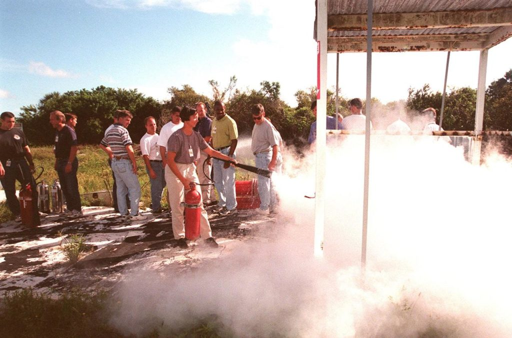KENNEDY SPACE CENTER, FLA. -- On the grounds of the Kennedy Space Center, members of the 1998 astronaut candidate class (Group 17) watch as candidate Patricia C. Hilliard (M.D.) practices using firefighting equipment during fire training. The class is at KSC for training activities, including a flight awareness program, plus touring the OPF, VAB, SSPF, SSME Processing Facility, launch pads, SLF, Apollo/Saturn V Center, and the crew quarters. The other U.S. candidates in the '98 class are Clayton C. Anderson, Lee J. Archambault, Tracy E. Caldwell (Ph.D.), Gregory E. Chamitoff (Ph.D.), Timothy J. Creamer, Christopher J. Ferguson, Michael J. Foreman, Michael E. Fossum, Kenneth T. Ham, Gregory C. Johnson, Gregory H. Johnson, Stanley G. Love (Ph.D.), Leland D. Melvin, Barbara R. Morgan, William A. Oefelein, John D. Olivas (Ph.D.), Nicholas J.M. Patrick (Ph.D.), Alan G. Poindexter, Garrett E. Reisman (Ph.D.), Steven R. Swanson, Douglas H. Wheelock, Sunita L. Williams, Neil W. Woodward III, George D. Zamka; and the international candidates are Leopold Eyharts, Paolo Nespoli, Hans Schlegel, Roberto Vittori, Bjarni V. Tryggvason, and Marcos Pontes KSC-99pp1163
