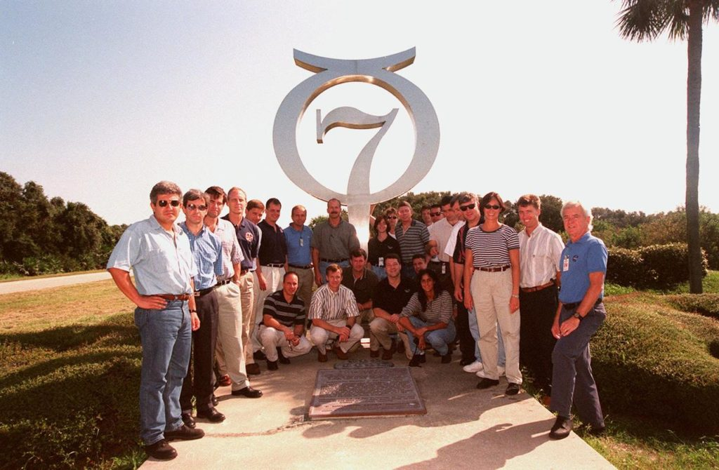 At Cape Canaveral Air Station, members of the 1998 astronaut candidate class (Group 17) pose in front of the Project Mercury monument at Launch Complex 14 during a tour of the station's facilities. This 13-foot-high astronomical symbol for the planet Mercury was constructed by General Dynamics, the Atlas airframe contractor, and dedicated in 1964 in honor of those who flew in the Mercury 7 capsule. The class is at Kennedy Space Center taking part in training activities, including a flight awareness program, as well as touring the OPF, VAB, SSPF, SSME Processing Facility, launch pads, SLF, Apollo/Saturn V Center, and the crew quarters. The U.S. candidates in the '98 class are Clayton C. Anderson, Lee J. Archambault, Tracy E. Caldwell (Ph.D.), Gregory E. Chamitoff (Ph.D.), Timothy J. Creamer, Christopher J. Ferguson, Michael J. Foreman, Michael E. Fossum, Kenneth T. Ham, Patricia C. Hilliard (M.D.), Gregory C. Johnson, Gregory H. Johnson, Stanley G. Love (Ph.D.), Leland D. Melvin, Barbara R. Morgan, William A. Oefelein, John D. Olivas (Ph.D.), Nicholas J.M. Patrick (Ph.D.), Alan G. Poindexter, Garrett E. Reisman (Ph.D.), Steven R. Swanson, Douglas H. Wheelock, Sunita L. Williams, Neil W. Woodward III, George D. Zamka; and the international candidates are Leopold Eyharts, Paolo Nespoli, Hans Schlegel, Roberto Vittori, Bjarni V. Tryggvason, and Marcos Pontes KSC-99pp1171