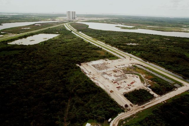 An aerial view reveals (foreground) the ongoing construction of an $8 million Reusable Launch Vehicle (RLV) Support Complex at Kennedy Space Center. At left is a multi-purpose hangar and at right a building for related ground support equipment and administrative/ technical support. In the background is the Vehicle Assembly Building. The road at right is the tow-way. The RLV complex will be available to accommodate the Space Shuttle; the X-34 RLV technology demonstrator; the L-1011 carrier aircraft for Pegasus and X-34; and other RLV and X-vehicle programs. The complex is jointly funded by the Spaceport Florida Authority, NASA's Space Shuttle Program and KSC. The facility will be operational in early 2000. KSC-99PP-1212