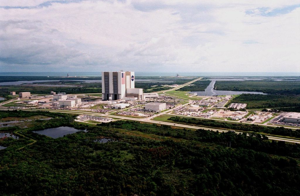 An aerial view of Launch Complex 39 Area shows the Vehicle Assembly Building (center), surrounded by (right) the Launch Control Center, (lower area, left to right) the Orbiter Processing Facility, Process Control Center and Operations Support Building. Looking toward the Atlantic Ocean (top) can be seen Launch Pads 39-A (right) and 39-B. The crawlerway stretches between the VAB and the launch pads. To the right of the crawlerway is the turn basin where new external tanks are brought from Louisiana via ship. The road bordering the buildings is Kennedy Parkway North. KSC-99PP-1214