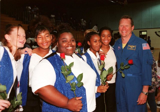 Dr. David Brown (right), a NASA astronaut, poses with students in the gymnasium of Ronald McNair Magnet School in Cocoa, Fla. From left, the students are Kristin Rexford, Danitra Anderson, Dominique Smith, Fallon Davis, and Qiana Taylor. Brown was at the school to attend a tribute to NASA astronaut Ronald McNair. The school had previously been renamed for the fallen astronaut who was one of a crew of seven, who lost their lives during an accident following launch of the Space Shuttle Challenger in January 1986 KSC-99pp1237