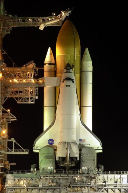 "In the early morning hours, Space Shuttle Discovery is framed with light from the Fixed Service Structure on Launch Pad 39B as it waits for flight and mission STS-103. At the top is seen the external tank gaseous oxygen vent arm system with the vent hood (commonly called the ""beanie cap"") poised above the external tank. The retractable arm and the beanie cap are designed to vent gaseous oxygen vapors away from the Space Shuttle. The arm truss section is 65 feet long and the diameter of the vent hood is 13 feet. Extending toward the cabin of the orbiter below is the orbiter access arm, with the environmental chamber (called the White Room) at the end. Through this chamber the crew enters the orbiter. The STS-103 mission, to service the Hubble Space Telescope, is scheduled for launch Dec. 17 at 8:47 p.m. EST. Mission objectives include replacing gyroscopes and an old computer, installing another solid state recorder, and replacing damaged insulation in the telescope. The mission is expected to last about 8 days and 21 hours. Discovery is expected to land at KSC Sunday, Dec. 26, at about 6:25 p.m. EST KSC-99padig046"