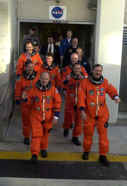 For the second time in two days, the STS-103 crew in their launch and entry suits eagerly head out of the Operations and Checkout Building on their way to Launch Pad 39B and liftoff of Space Shuttle Discovery. From front to back by two's are Pilot Scott J. Kelly and Commander Curtis L. Brown Jr., Mission Specialists John M. Grunsfeld (Ph.D.) and Jean-Francois Clervoy of France, C. Michael Foale (Ph.D.) and Claude Nicollier of Switzerland, and Steven L. Smith taking up the rear. The previous launch attempt on Dec. 17 was scrubbed about 8:52 p.m. due to numerous violations of weather launch commit criteria at KSC. The mission, to service the Hubble Space Telescope, is now scheduled for launch Dec. 19 at 7:50 p.m. EST from Launch Pad 39B. Mission objectives include replacing gyroscopes and an old computer, installing another solid state recorder, and replacing damaged insulation in the telescope. After the 7-day, 21-hour mission, Discovery is expected to land at KSC Monday, Dec. 27, at about 5:24 p.m. EST KSC-99padig051