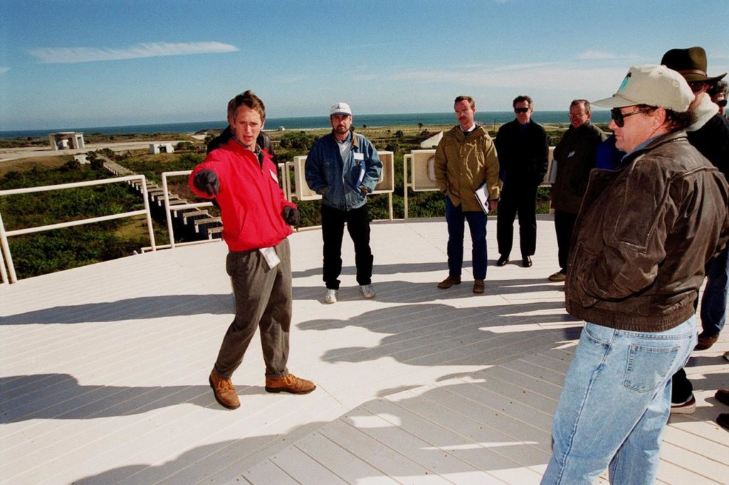 On top of the block house at Launch Complex 34, representatives from environmental and Federal agencies hear from Laymon Gray, with Florida State University, about the environmental research project that involves the Department of Defense, Environmental Protection Agency, Department of Energy and NASA in a groundwater cleanup effort. Concentrations of trichloroethylene solvent have been identified in the soil at the complex as a result of cleaning methods for rocket parts during the Apollo Program, which used the complex, in the 60s. The group formed the Interagency NDAPL Consortium (IDC) to study three contamination cleanup technologies: Six Phase Soil Heating, Steam Injection and In Situ Oxidation with Potassium Permanganate. All three methods may offer a way to remove the contaminants in months instead of decades. In the background (left) can be seen the cement platform and walkway from the block house to the pad. Beyond it is the Atlantic Ocean. KSC hosted a two-day conference that presented information and demonstrations of the three technologies being tested at the site KSC00pp0103