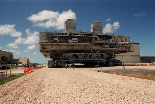 KENNEDY SPACE CENTER, FLA. -- A crawler-transporter with mobile launcher platform on top makes its way from the Orbiter Processing Facility along the once-buried portion of the Apollo-era crawlerway leading to the Vehicle Assembly Building (VAB) high bay. The road was restored as part of KSC's Safe Haven project. High bay 2 provides a third stacking area.. The primary goal of the Safe Haven construction project was to strengthen readiness for hurricane season by expanding the VAB's storage capacity. The new area, in high bay 2, will allow NASA to preassemble stacks and still have room in the VAB to pull a Shuttle back from the pad if severe weather threatens. Potential rollouts of the Space Shuttle to the launch pad from high bay 2 will involve making a turn around the north side of the VAB in contrast to the straight rollouts from high bays 1 and 3, on the east side of the VAB facing the launch pads KSC-00pp0717